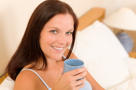 Bedroom - young woman drink coffee lying in white bed photo