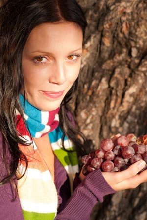 Winter outfit portrait of beautiful female model posing with grapes photo