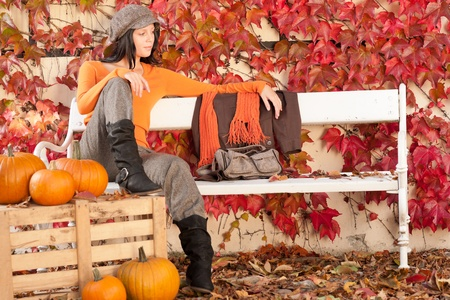 Autumn park young woman relax sitting on bench with pumpkins photo
