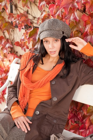 Autumn park scenery young woman relax on bench looking aside photo