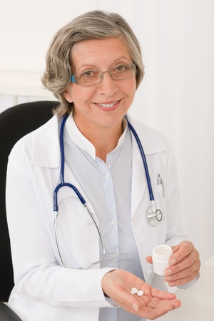 Medical doctor senior female holding pills smiling professional portrait photo