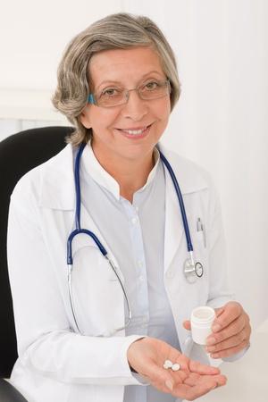 Medical doctor senior female holding pills smiling professional portrait photo