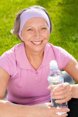Senior sportive woman smiling relax with water sunny outdoor photo