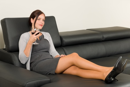 red couch: Elegant businesswoman sitting on leather sofa drink glass red wine