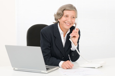 Smiling successful senior businesswoman sitting behind office table portrait Stock Photo - 11109718
