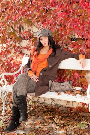 Autumn park scenery young woman relax on bench fashion model photo