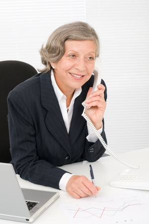 Smiling successful senior businesswoman sitting behind office table portrait photo