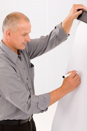 Handsome mature businessman writing at empty flip chart looking aside photo