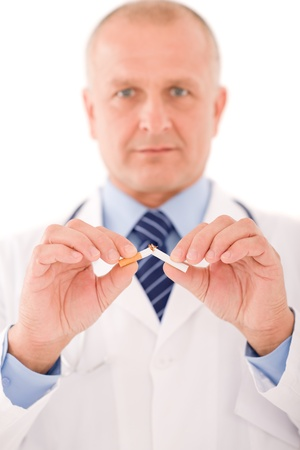 Stop smoking mature doctor male breaks  cigarette focus on hand photo
