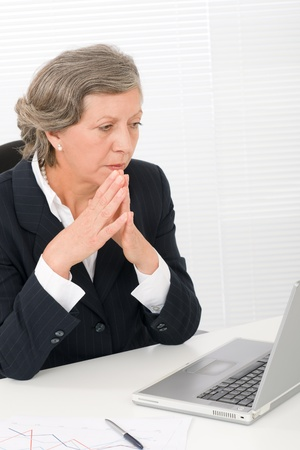 Senior businesswoman looking seriously at computer sitting behind office table Stock Photo - 11109961