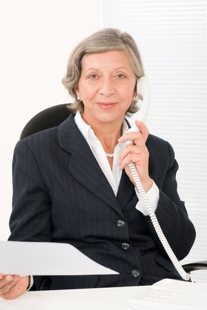 Senior professional businesswoman on phone hold empty sheet Stock Photo - 11109977