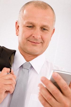 Mature handsome businessman wear suit looking at phone close-up portrait photo