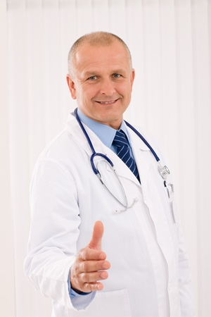 Happy mature doctor male giving handshake welcoming portrait photo