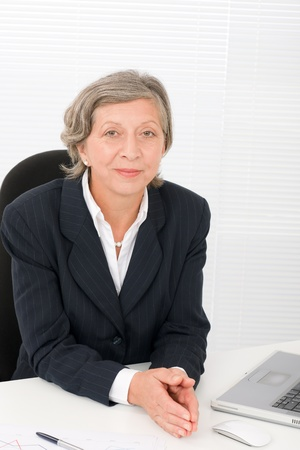 Successful senior businesswoman sitting behind office table with laptop portrait Stock Photo - 11109986