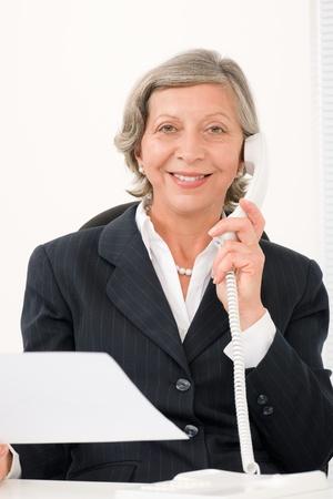 Senior professional businesswoman on phone hold empty sheet smiling Stock Photo - 11109990