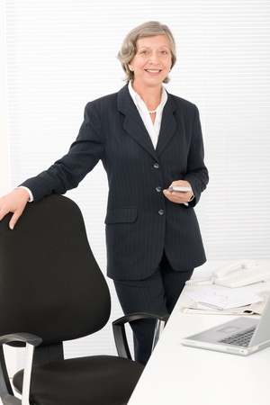 Smiling successful senior businesswoman standing behind office table portrait Stock Photo - 11109989