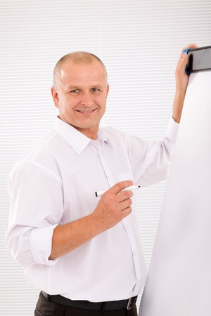 Handsome mature businessman writing at empty flip chart looking front photo