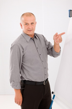 Mature handsome businessman pointing at empty flip chart looking front photo
