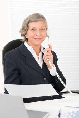 Senior professional businesswoman on phone hold empty sheet smiling Stock Photo - 11148567