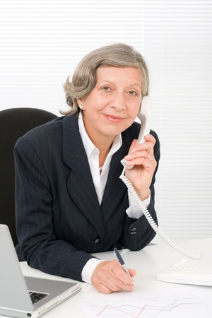 Smiling successful senior businesswoman sitting behind office table portrait Stock Photo - 11148564
