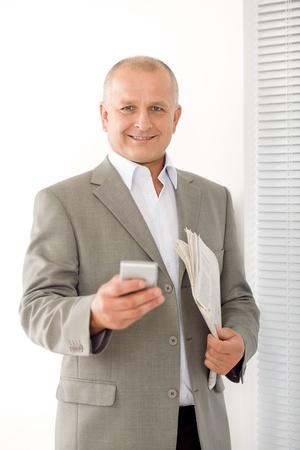 Handsome mature businessman smiling holding phone close-up professional portrait photo