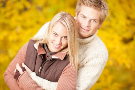 Autumn smiling young couple in love hugging in park together photo