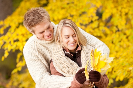 Young playful couple happy picking leaves in autumn park outfit photo