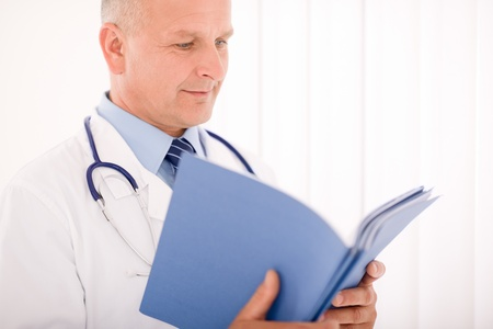 naar beneden kijken: Professionele senior arts man met stethoscoop naar beneden kijken documentmappen