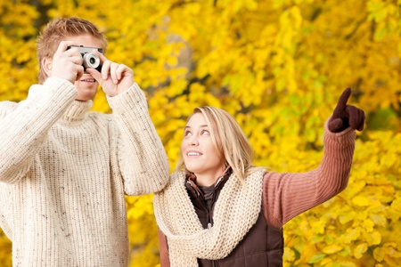 Young happy couple making photo in autumn park pointing at photo