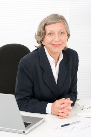 Successful senior businesswoman sitting behind office table with laptop portrait Stock Photo - 11174404