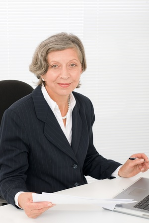 Successful senior businesswoman sitting behind office table with laptop portrait Stock Photo - 11287811