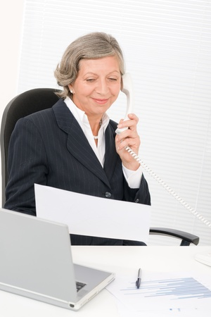 Senior professional businesswoman on phone hold empty sheet smiling Stock Photo - 11287812