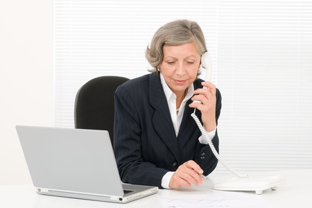 business woman phone: Serious successful senior businesswoman sitting behind office table portrait