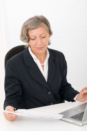 Successful senior businesswoman sitting behind office table with laptop portrait Stock Photo - 11287856