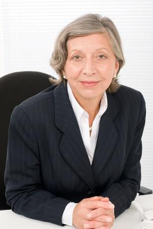 Successful senior businesswoman professional portrait watch camera sitting behind table Stock Photo - 11287882