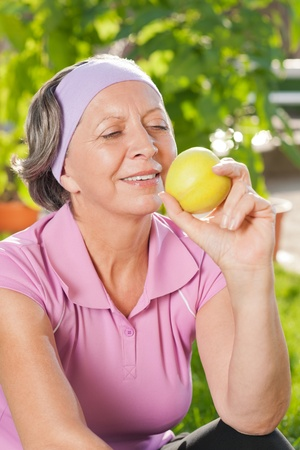 Senior sportive woman smiling eat apple outdoor sunny day photo