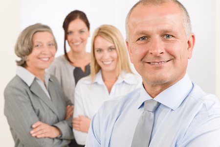 Business team senior businessman with attractive happy colleagues in office photo