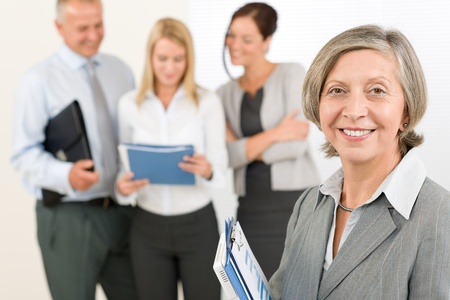 Business team senior businesswoman in front with attractive happy colleagues photo