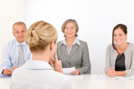 examined: Business interview young woman being examined by professional manager team