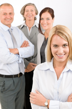 Business team attractive young businesswoman with happy mature colleagues photo