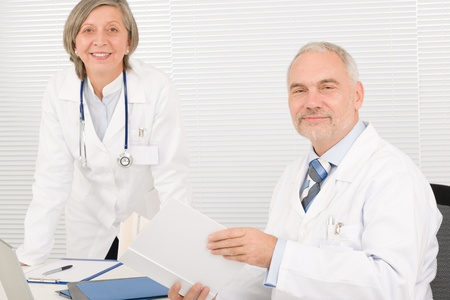 Medical senior doctor male reading book with professional female colleague photo