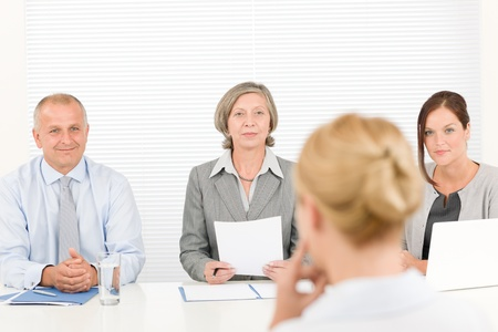 Business interview young woman being examined by professional manager team photo