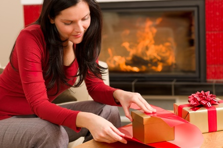 Happy woman in red wrapping christmas present by home fireplace Stock Photo - 11288015