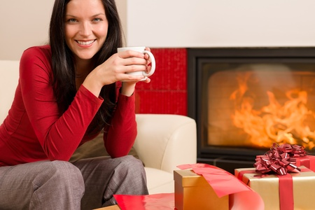 Happy woman wrapping Christmas present by fireplace enjoying hot drink Stock Photo - 11288014