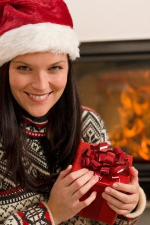 Xmas present happy woman by home fireplace wear Santa hat Stock Photo - 11288012