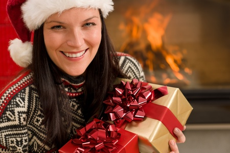 Xmas present happy woman by home fireplace wear Santa hat photo