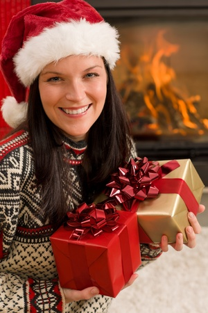 Xmas present happy woman by home fireplace wear Santa hat Stock Photo - 11288019
