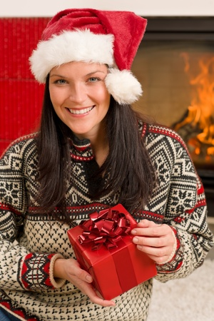 Xmas present happy woman by home fireplace wear Santa hat Stock Photo - 11288022