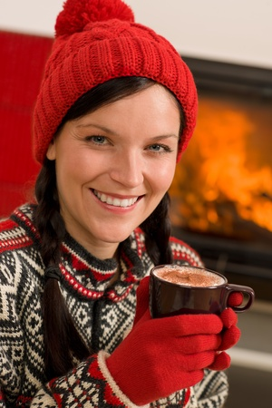 Winter christmas woman with hat and gloves drink by fireplace photo