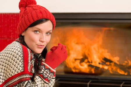 Happy woman warming up by home fireplace wear christmas sweater photo